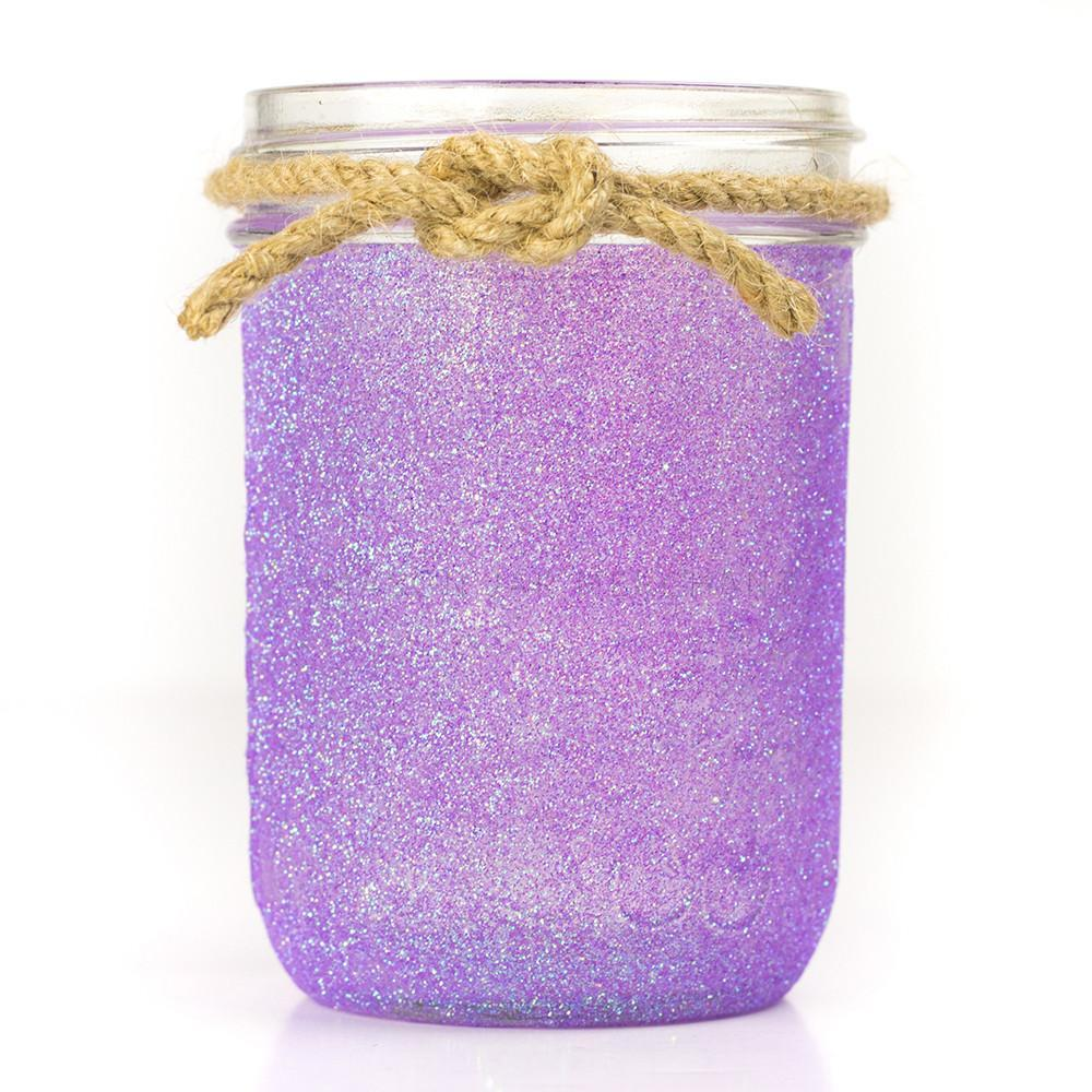 close up of a 16 oz glass reusable purple glitter mason jar with a piece of twine tied around the top