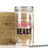 "24 oz reusable glass mason jar tumbler with a silver straw lid and a black and white reusable straw sits in front of an old piece of wood. On the jar are the words ""look like a"" in white block text, ""beauty"" in hot pink cursive, ""train like a"" in white block text and ""Beast"" in black shadow text"