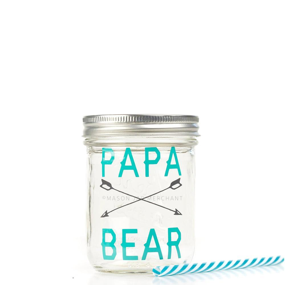 "16 oz reusable glass mason jar tumbler with a silver straw lid and a teal and white stripped reusable straw. On the jar are the words ""Papa Bear"" in teal and in between the words are two grey arrows crossing each other"