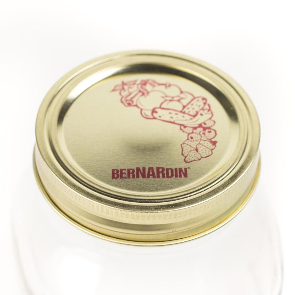 Close up photo of a Gold Bernardin Canning lid with red ink, shown on a white background.