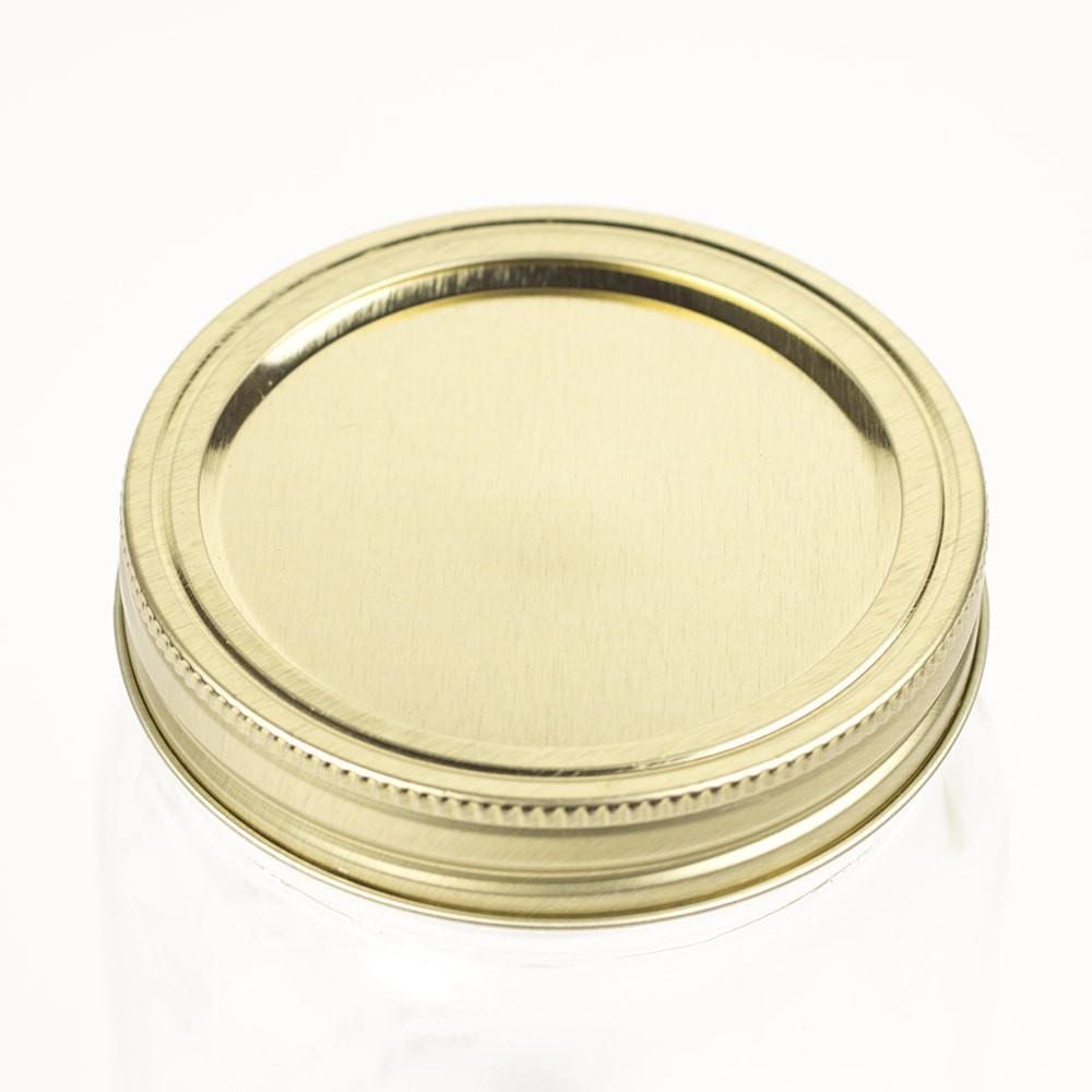 close up of a gold wide mouth canning lid and ring on a white background
