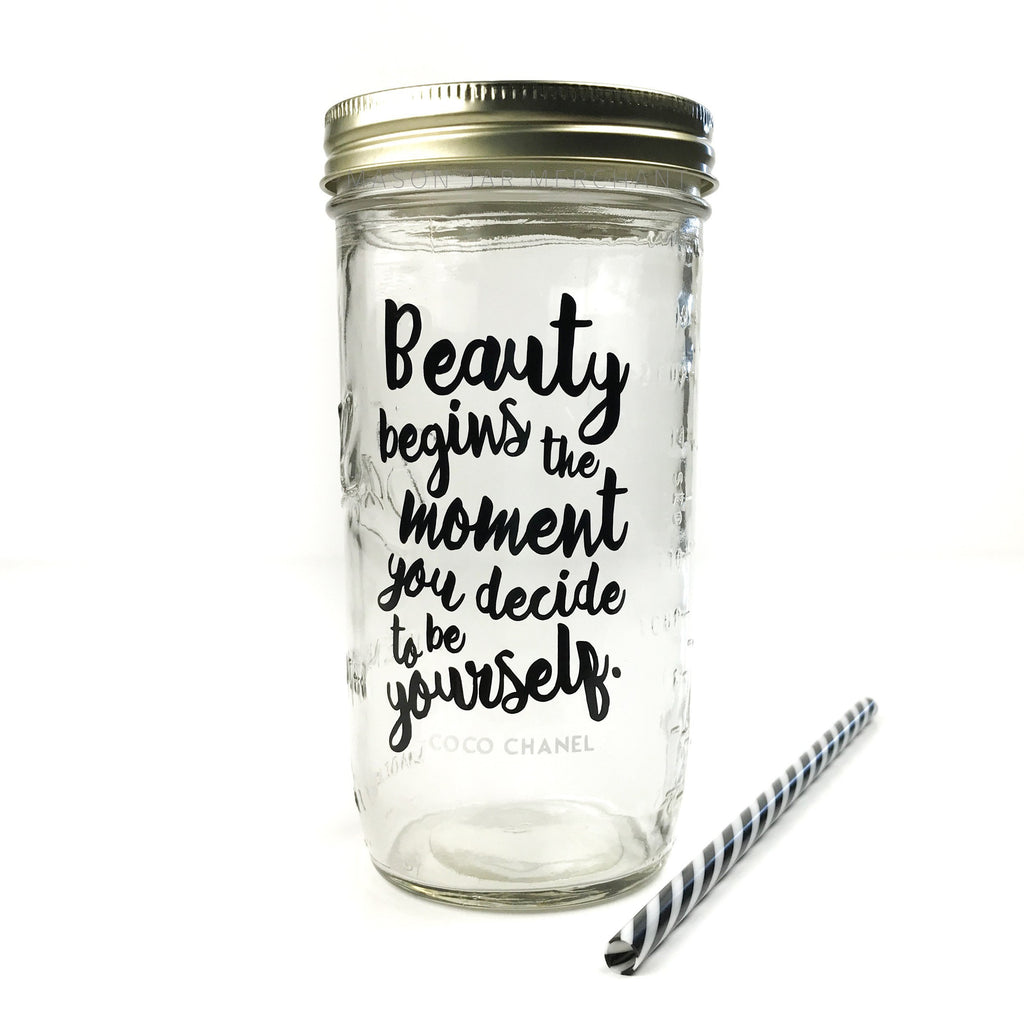 "24 oz reusable glass mason jar tumbler with gold straw lid and a black and white stripped reusable straw. Text on the jar says ""Beauty begins the moment you decide to be yourself"" in black cursive"
