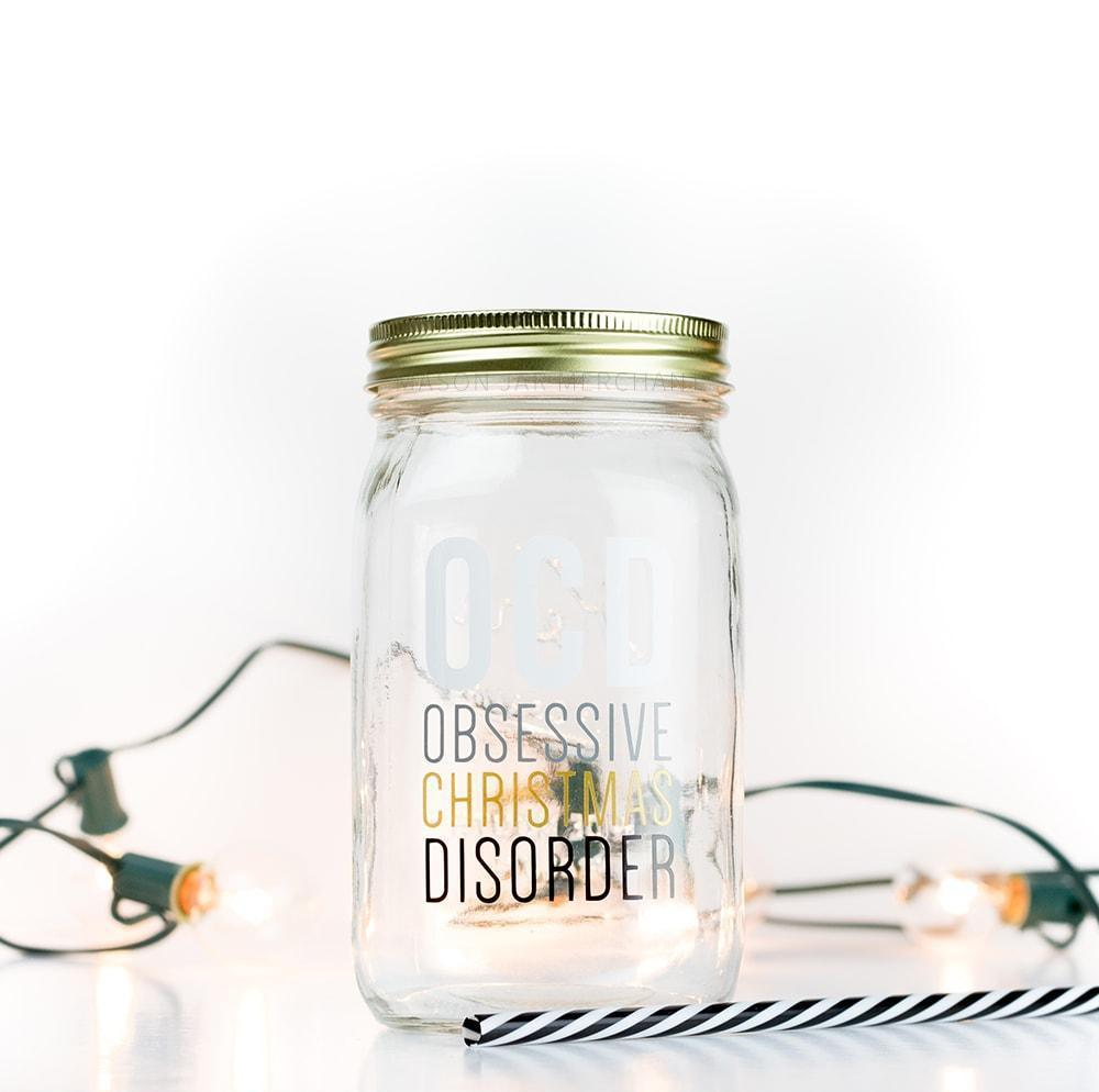 "32 oz reusable glass mason jar with gold straw lid and a black and white stripped straw sits on a white background with white Christmas lights. On the jar are the words ""OCD Obsessive Christmas Disorder"" in white, grey, gold and black block text"