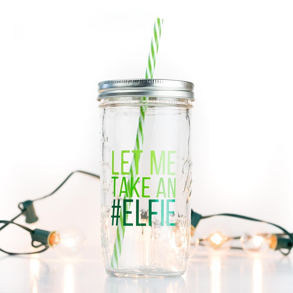 "24 oz reusable glass mason jar tumbler with a silver straw lid and a green and white reusable stripped straw sit on a white background with white lights. On the jar are the words ""let me"" in lime green block text, ""take an"" in green block text, and ""#elfie"" in sparkly dark green block text"