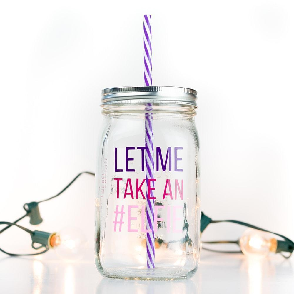 "32 oz reusable glass mason jar tumbler with a silver straw lid and a purple and white stripped reusable straw sit on a white background with white lights. On the jar are the word ""let me"" in purple block text, ""take an"" in hot pink block text and ""#Elfie"" in sparkly light pink block text"