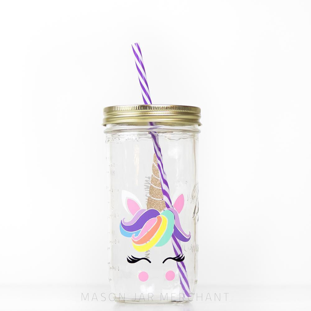 24 oz glass reusable mason jar tumbler with a gold straw lid and a purple and white stripped reusable straw. On the jar is the head of a unicorn with a colourful main and a sparkly gold horn, eyelashes and pink rosie cheeks
