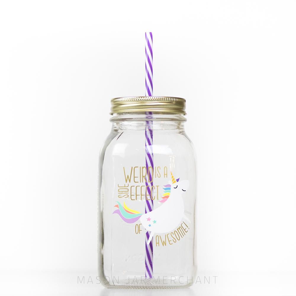"32 oz glass reusable mason jar tumbler with a gold regular mouth straw lid and a purple and white stripped straw. On the jar is a white unicorn with a colourful mane and tail. Beside it are the words ""weird is a side effect of awesome"" in gold text"