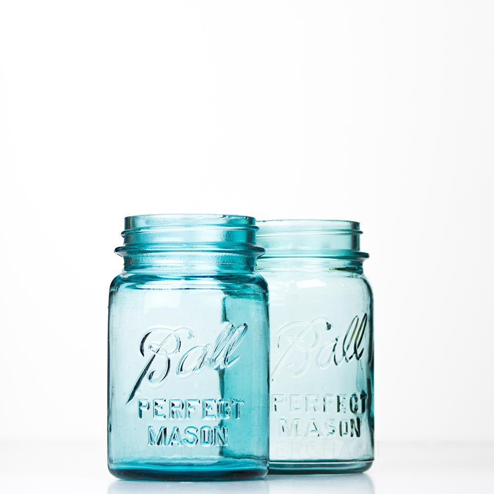 Two vintage blue Ball regular mouth pint mason jars against a white background