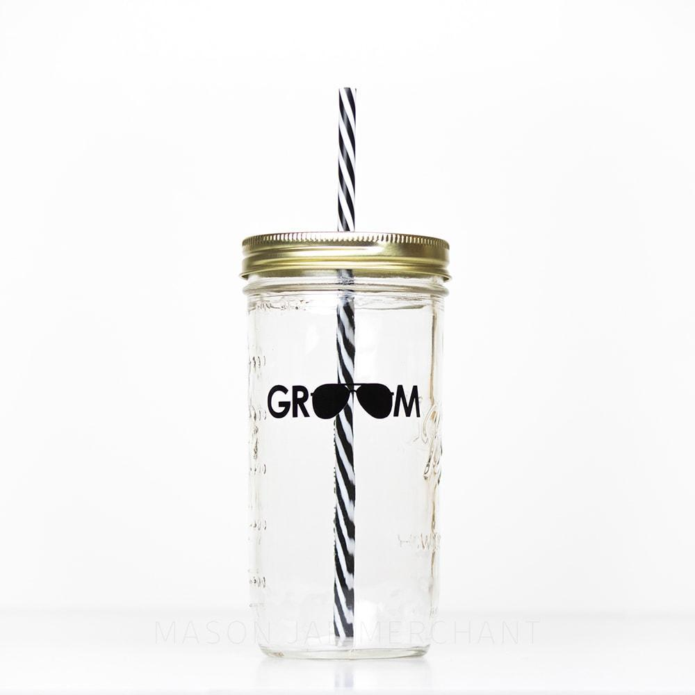"24 oz reusable glass mason jar tumbler with gold straw lid and a black and white stripped reusable straw. On the jar is the word ""GROOM"" in black text but the two o's are shaped like aviator sunglasses"