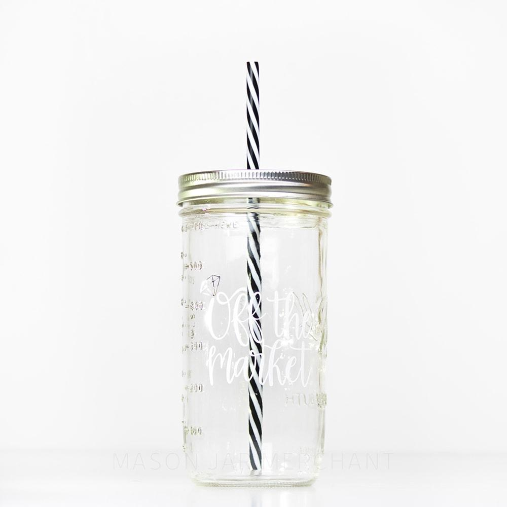 "24 oz reusable glass mason jar tumbler with a silver lid and a black and white stripped reusable straw. On the jar are the words ""Off the Market"" in white cursive, the O in ""off"" has a silver diamond on it to look like a ring"