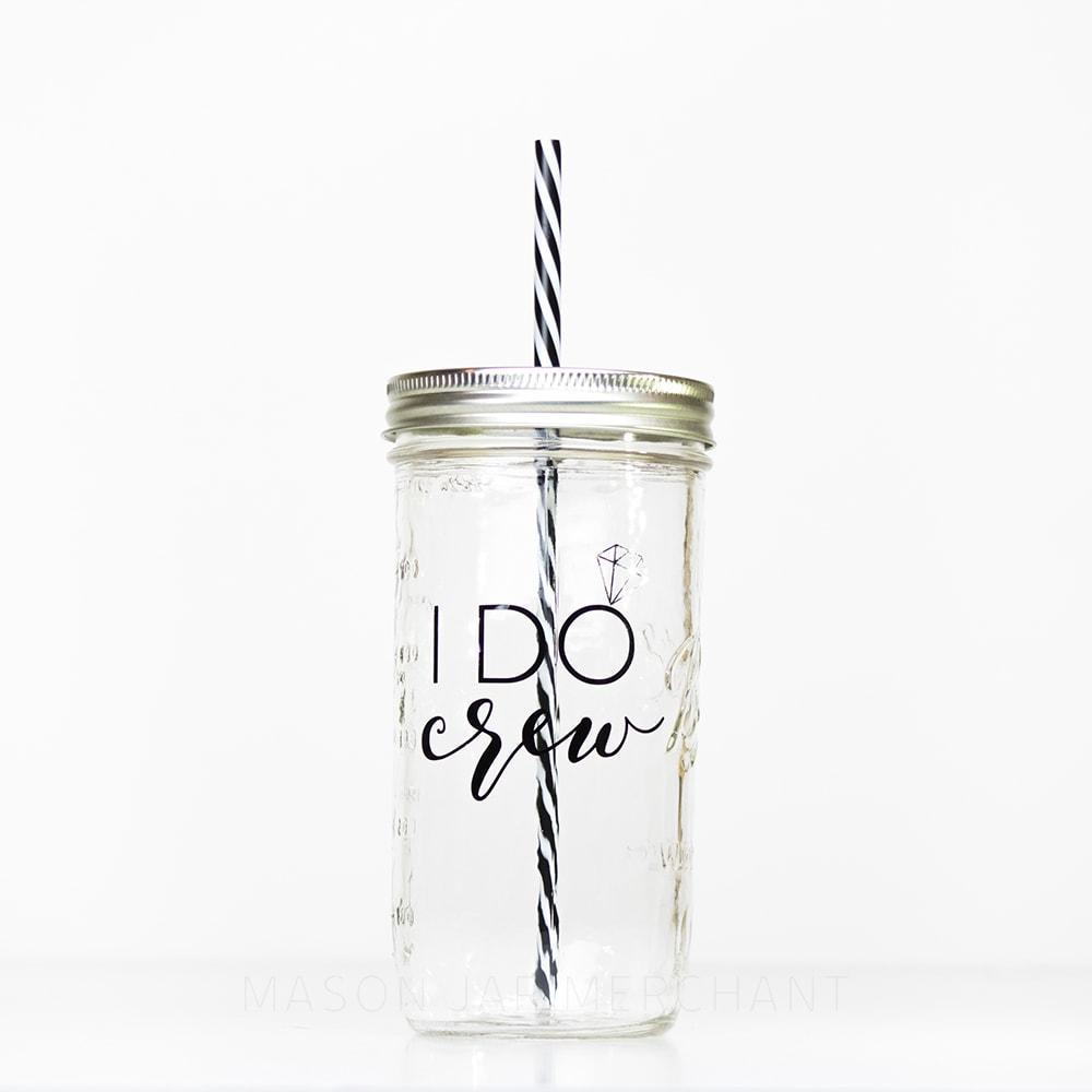 "24 oz reusable glass mason jar tumbler with a silver straw lid and a black and white stripped reusable straw sit on a white background. The words ""I DO"" are typed in thin black block text, there is a silver diamond on the O to make it look like a ring. Underneath that text is the word ""crew"" in black cursive."