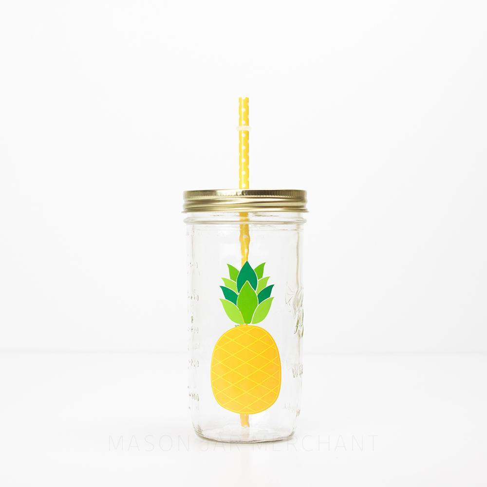 24 oz reusable glass mason jar tumbler with gold straw lid and a yellow reusable straw with white polkadots. On the jar is a picture of a yellow pineapple with green leaves