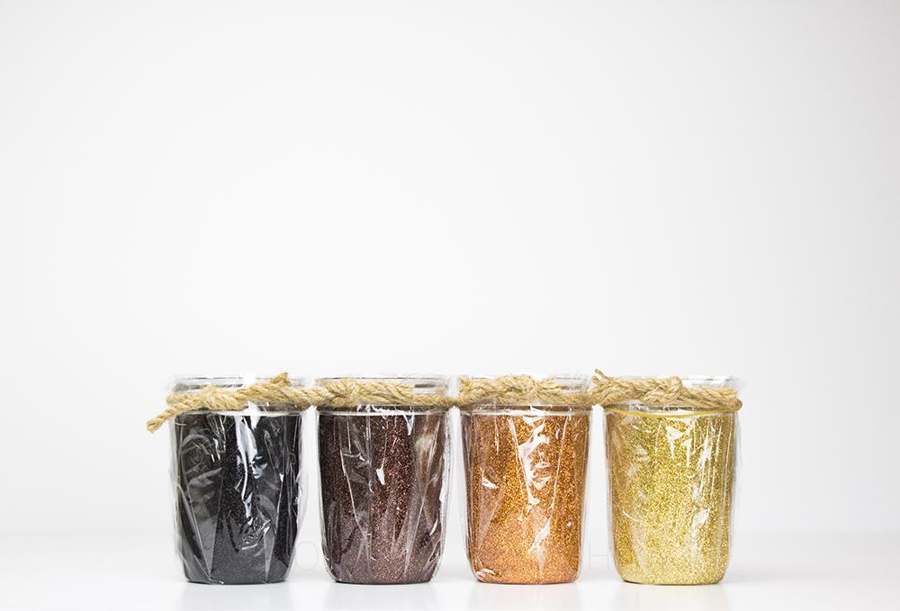 four glass reusable 8 oz mason jars sit in a line on a white background. On each jar is either dark brown, brown, orange or gold glitter. Each jar is covered with a plastic bag and tied with twine