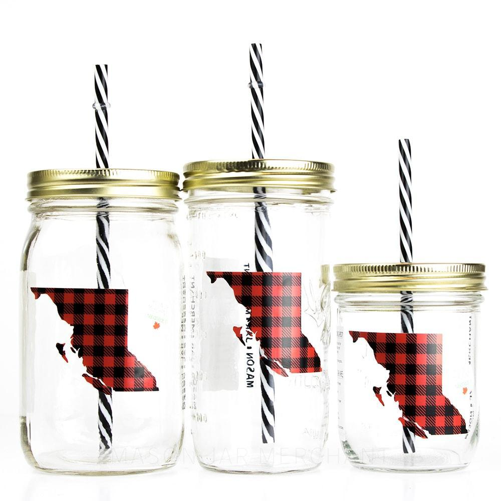 Three reusable glass mason jar tumblers, one 32 oz, 24 oz and 16 oz. All have gold straw lids and black and white stripped reusable straws. The picture on the jar is a red and black checkered map of British Columbia