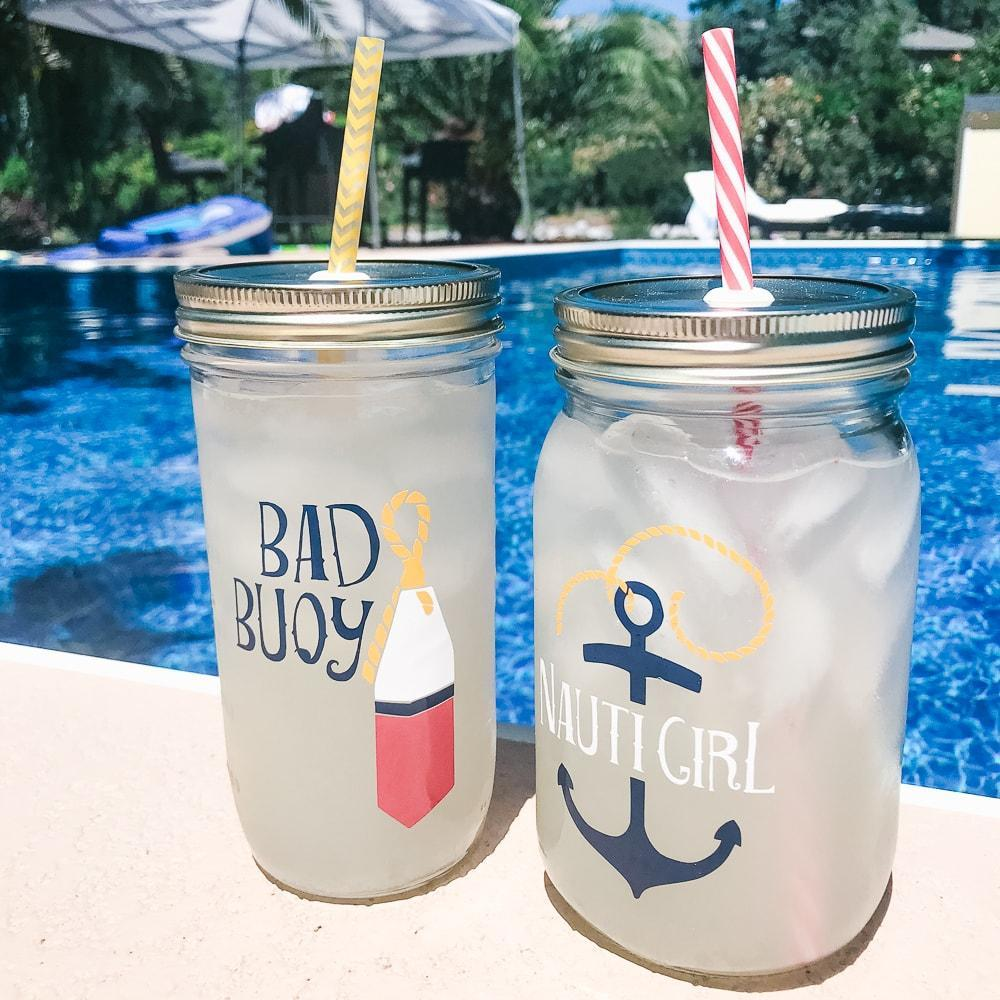 nautical themed his and hers glass reusable water bottles on a striped beach towel next to a pool