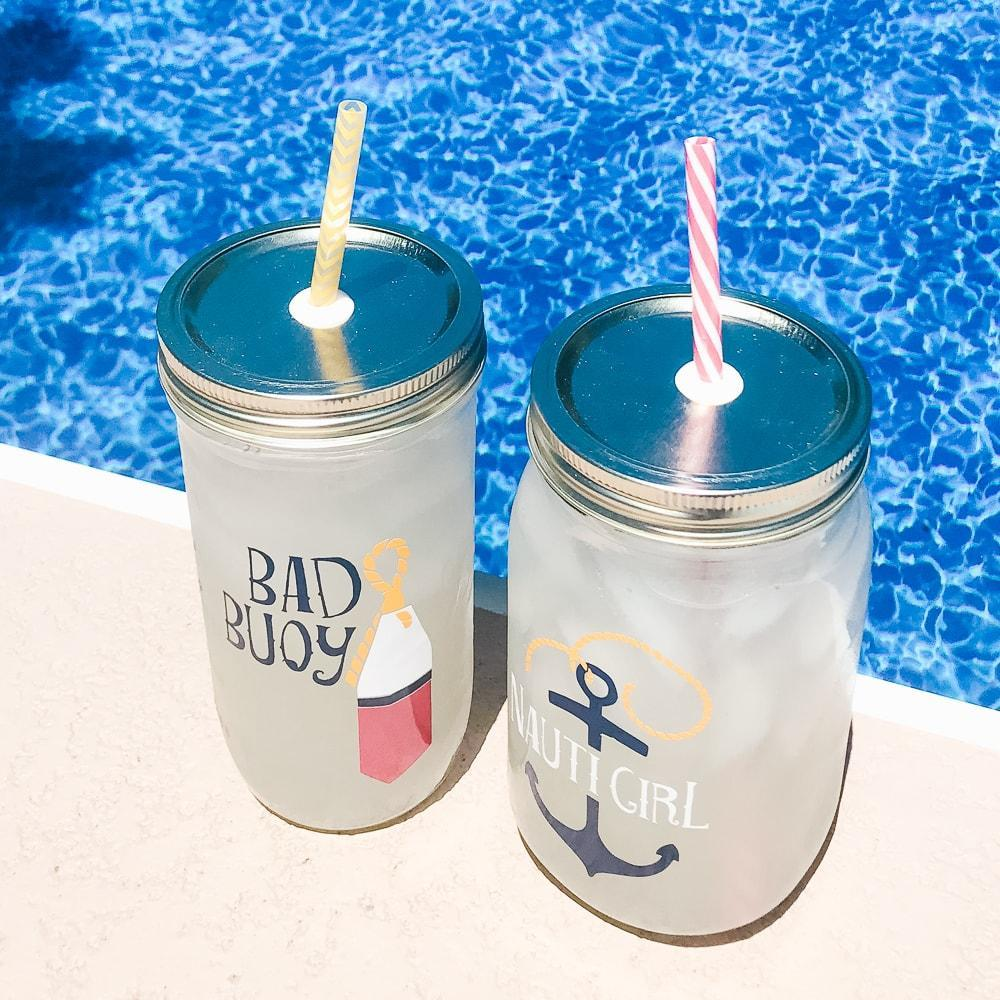 nautical reusable glass tumblers with reusable straws filled with ice and lemonade next to a pool