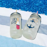 nautical themes his and hers glass reusable water bottles on a striped beach towel next to a pool
