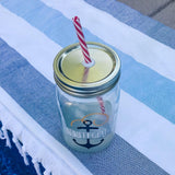 nautical reusable mason jar tumbler filled with ice and lemonade next to a pool