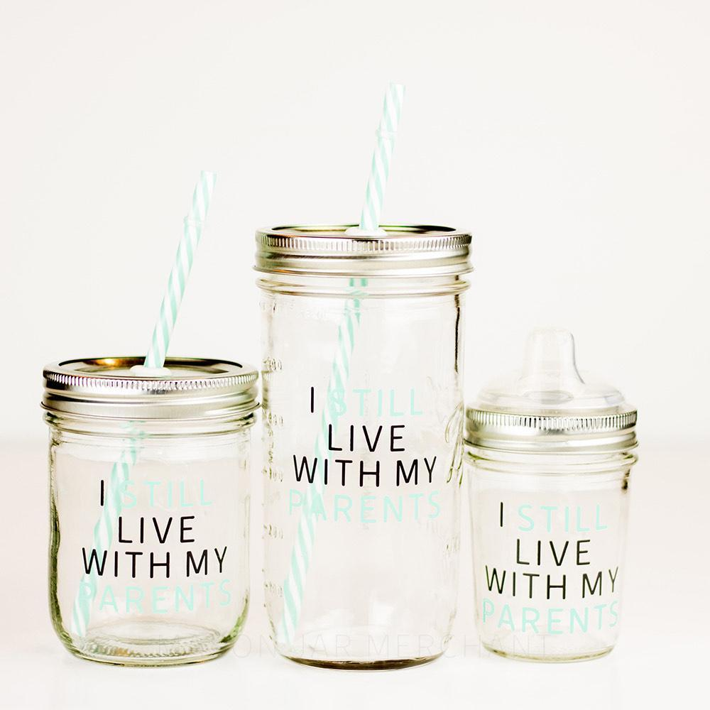 "Three reusable glass mason jar tumbler sits in a line on a white background. One 16 oz, 24 oz and 8 oz. All jars have a gold straw lid, the 16 & 24 oz have a aqua and white stripped reusable straw and the 8 oz has a clear sippy lid. All jars have the words ""I still live with my parents"" in black and aqua thin block text."