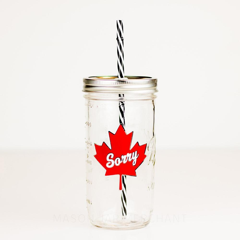 "24 oz glass reusable mason jar tumbler with a gold straw lid and a black and white stripped reusable straw sits on a white background. On the jar is a red maple leaf with the word ""sorry"" in white cursive text in the middle of it"