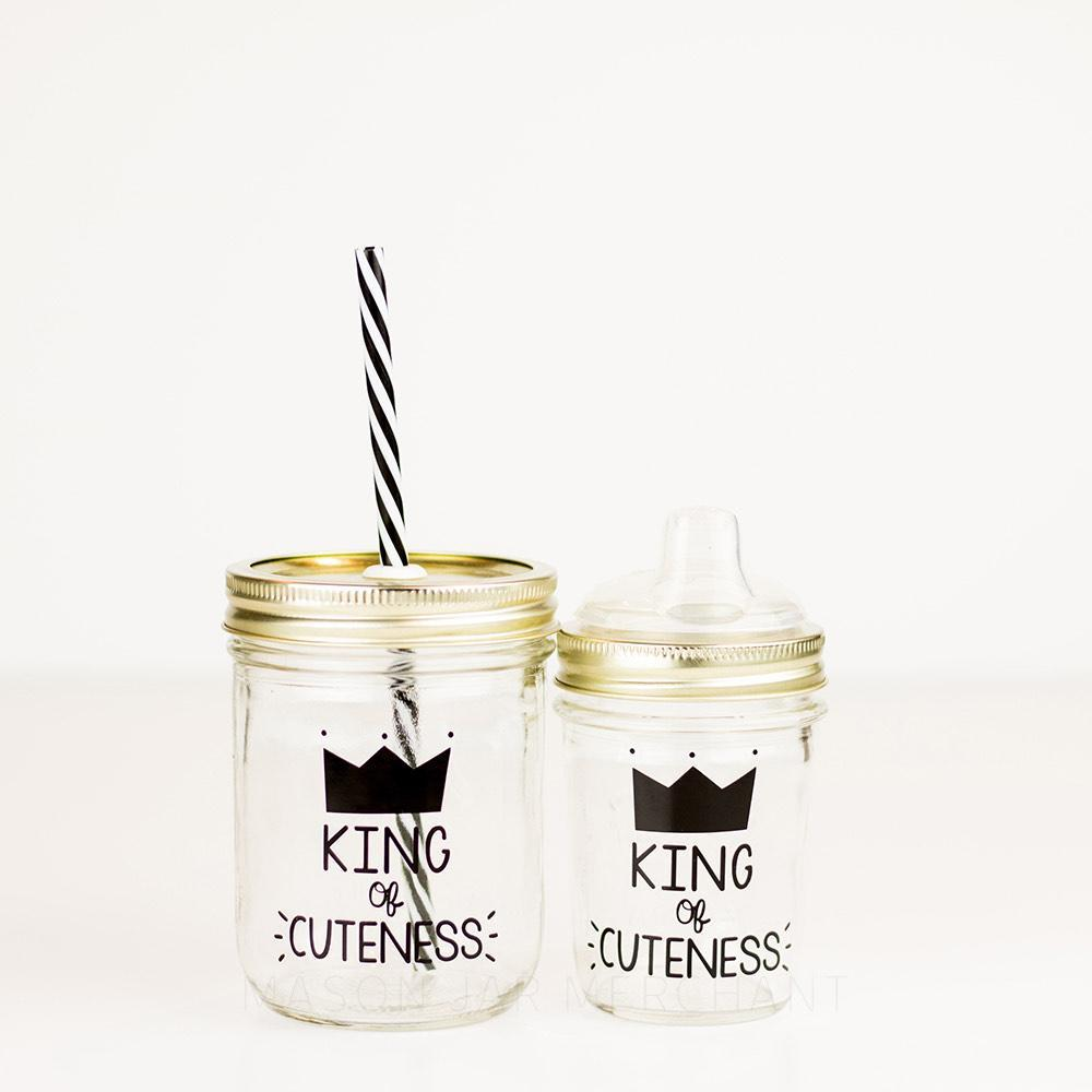 "16 & 8 oz reusable glass mason jars sits side by side, one has a gold straw lid with a black and white stripped reusable straw and the other has a gold lid with a siippy cup mouth piece. On the jar is a black crown and underneath are the words ""Kind of cuteness"" in black text"