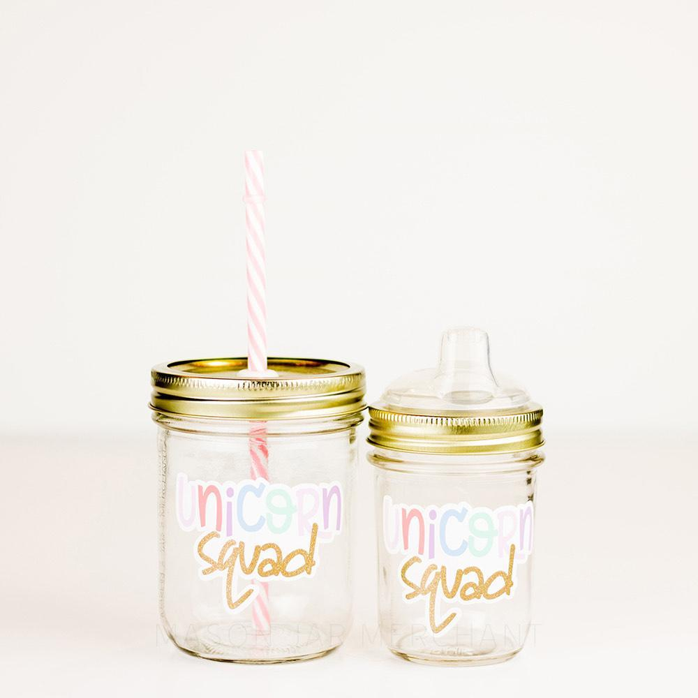 "One 16 oz and one 8 oz glass reusable mason jar tumblers sit next to each other. Both have gold lids, one with a straw lid and the other with a rubber bottle lid. There is a pink and white stripped reusable straw in the straw lid. On both jars are the words ""unicorn squad""  in light rainbow colours. The last word is in gold"