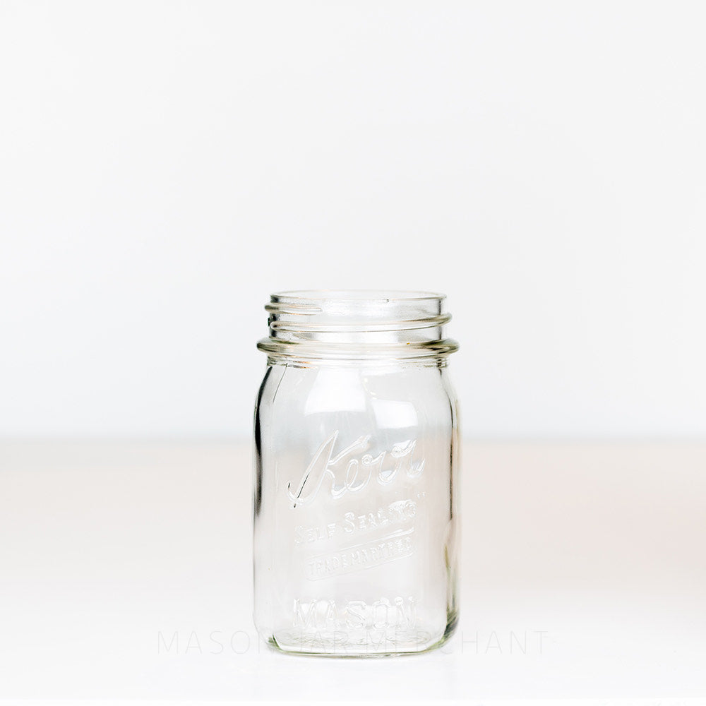 Vintage regular mouth pint mason jar with Kerr  self-sealing logo, against a white background