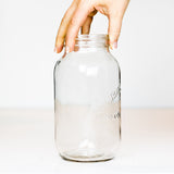 Side view of a hand holding a Bernardin regular mouth quart mason jar