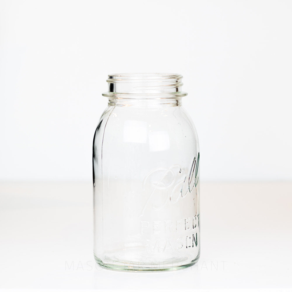 Side view of a vintage Ball quart mason jar against a white background