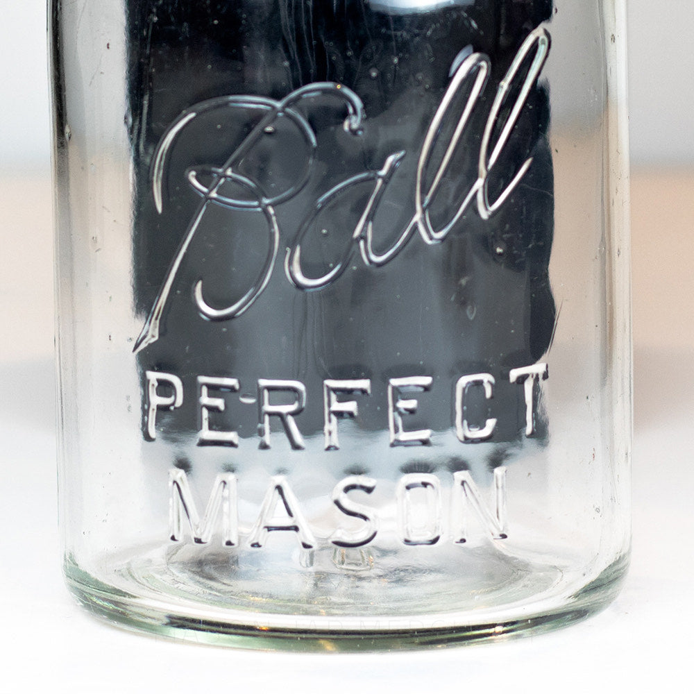Close-up of the Ball Perfect Mason logo on a vintage quart Ball mason jar