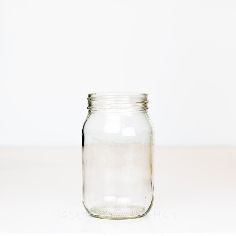 Regular mouth pint mason jar with plain sides on a white background
