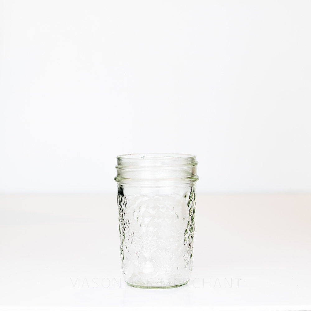 A half pint regular mouth mason jar with a fruit pattern against a white background