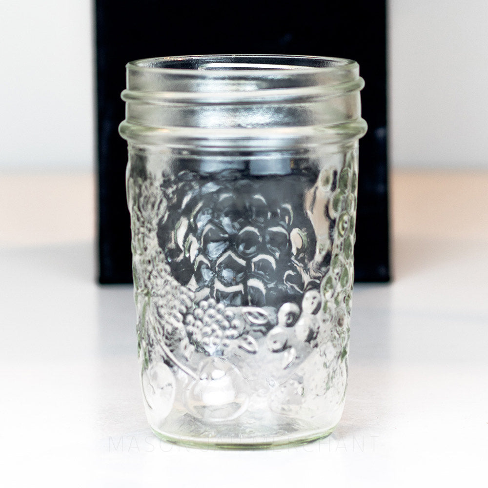 A half pint regular mouth mason jar with a fruit pattern against a black backdrop
