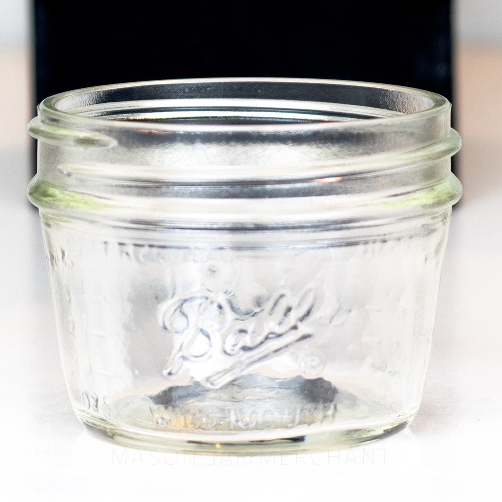 Wide mouth Ball half pint mason jar with Ball logo against a black backdrop