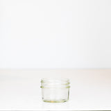 Adorable 2 oz. regular mouth mason jar with straight sides on a white background, perfect for spices!
