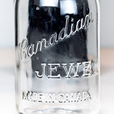 Close-up of a Canadian Jewel logo on a vintage gem mouth mason jar