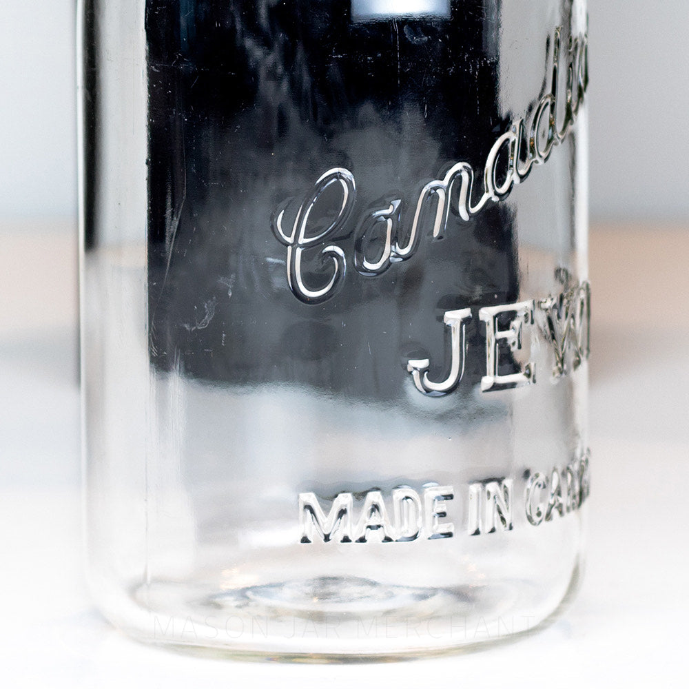 Side view close-up of a Canadian Jewel logo on a vintage gem mouth quart mason jar