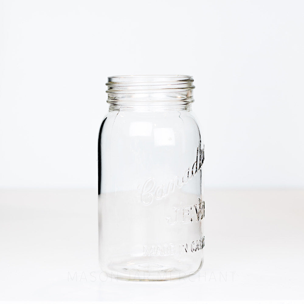 Side view of a vintage Jewel gem mouth quart mason jar against a white background