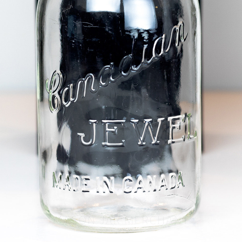Close-up of Canadian Jewel logo on a vintage gem mouth quart jar
