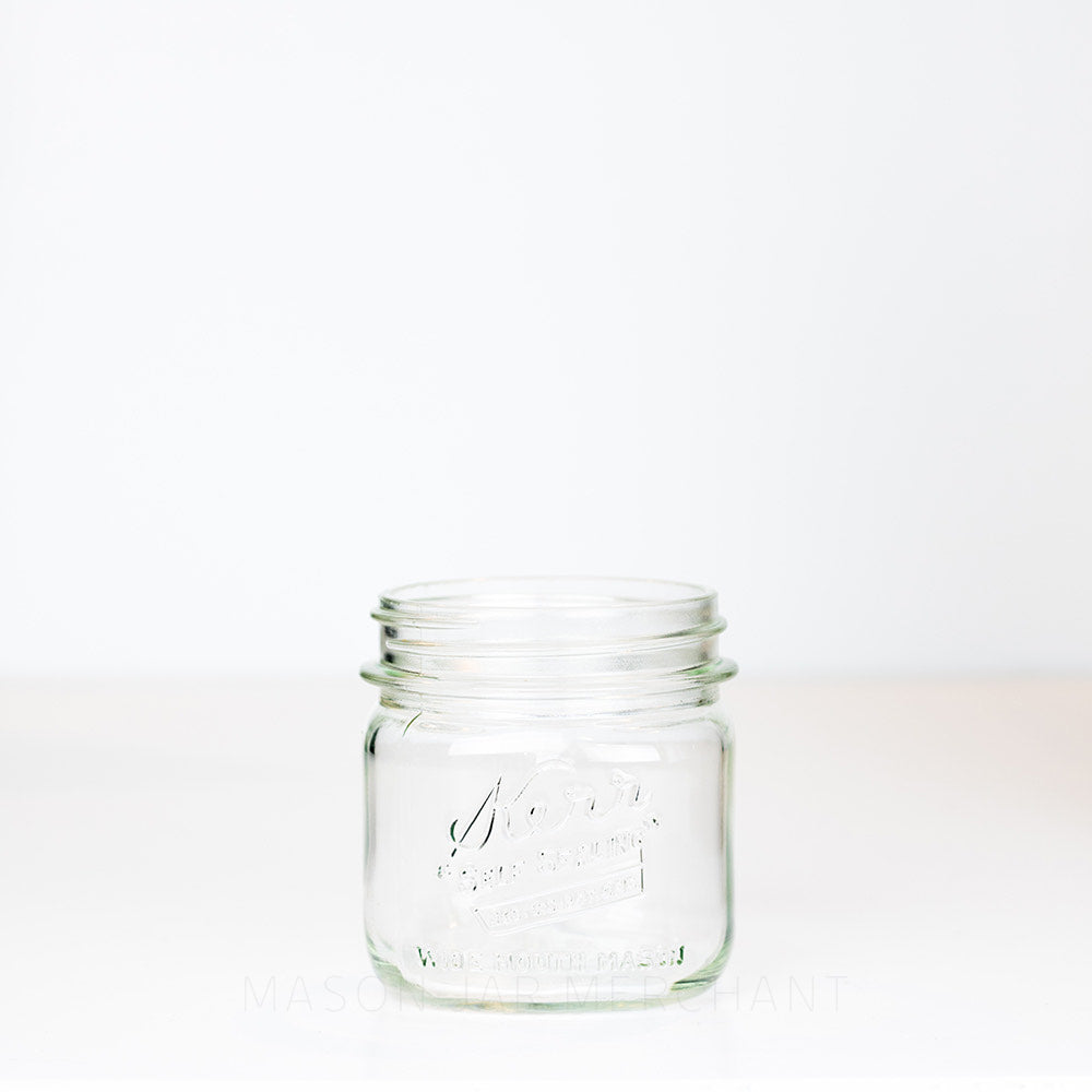 "Kerr wide mouth pint mason jar with ""self-sealing"" logo, against a white background"