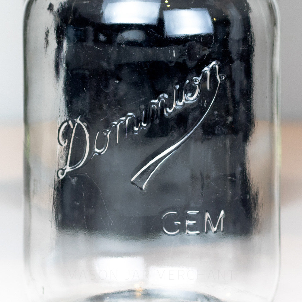 Close up of a mason jar with a Dominion (Underlined Style) GEM raised logo on a black background