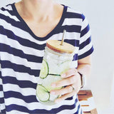 woman in a navy and white striped shirt holding a reusable glass tumbler with a handmade bamboo straw lid and stainless steel reusable straw