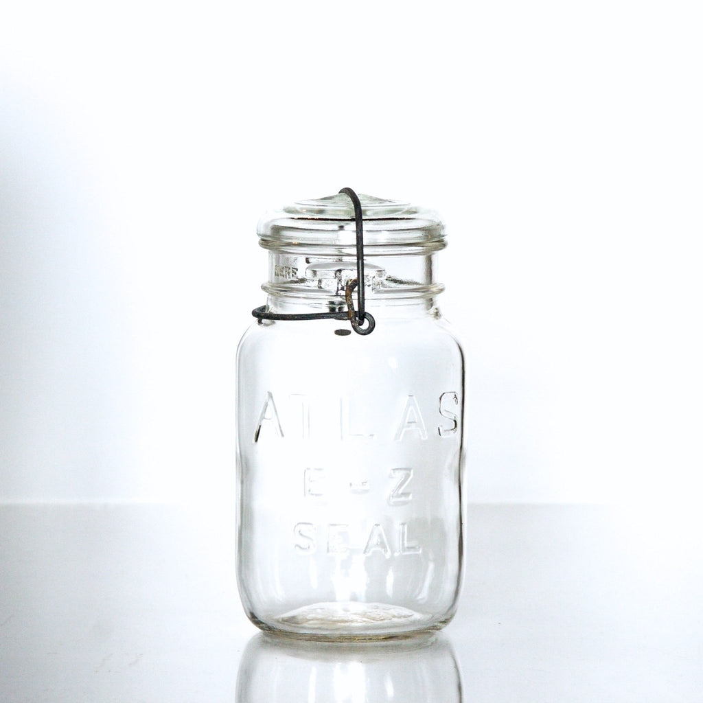 Vintage Atlas E-Z Seal quart mason jar with  wire bail and glass lid, against a white background