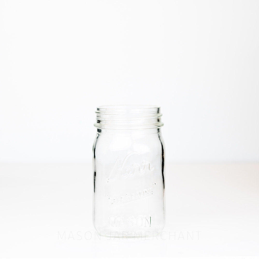 Kerr regular mouth pint mason jar with Self-sealing logo against a white background
