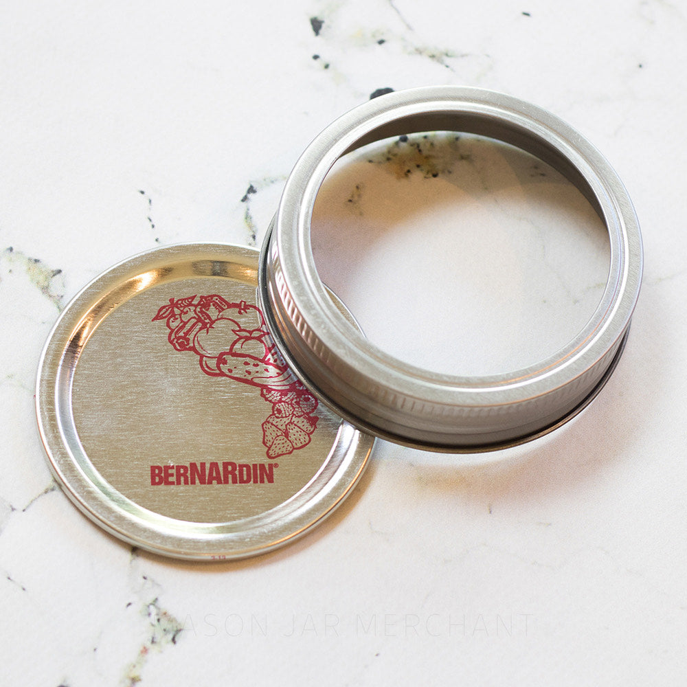 close up of a silver Bernardin Gem mouth canning lid and ring with red print on a white marble background