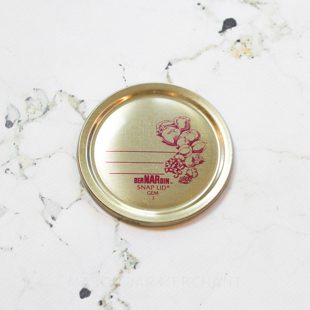 gold Bernardin GEM mouth flat lid with red fruit image and red lines on a white marble countertop