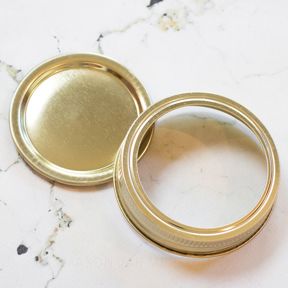 Close up of a gold plain Gem mouth canning lid and ring on a white marble background