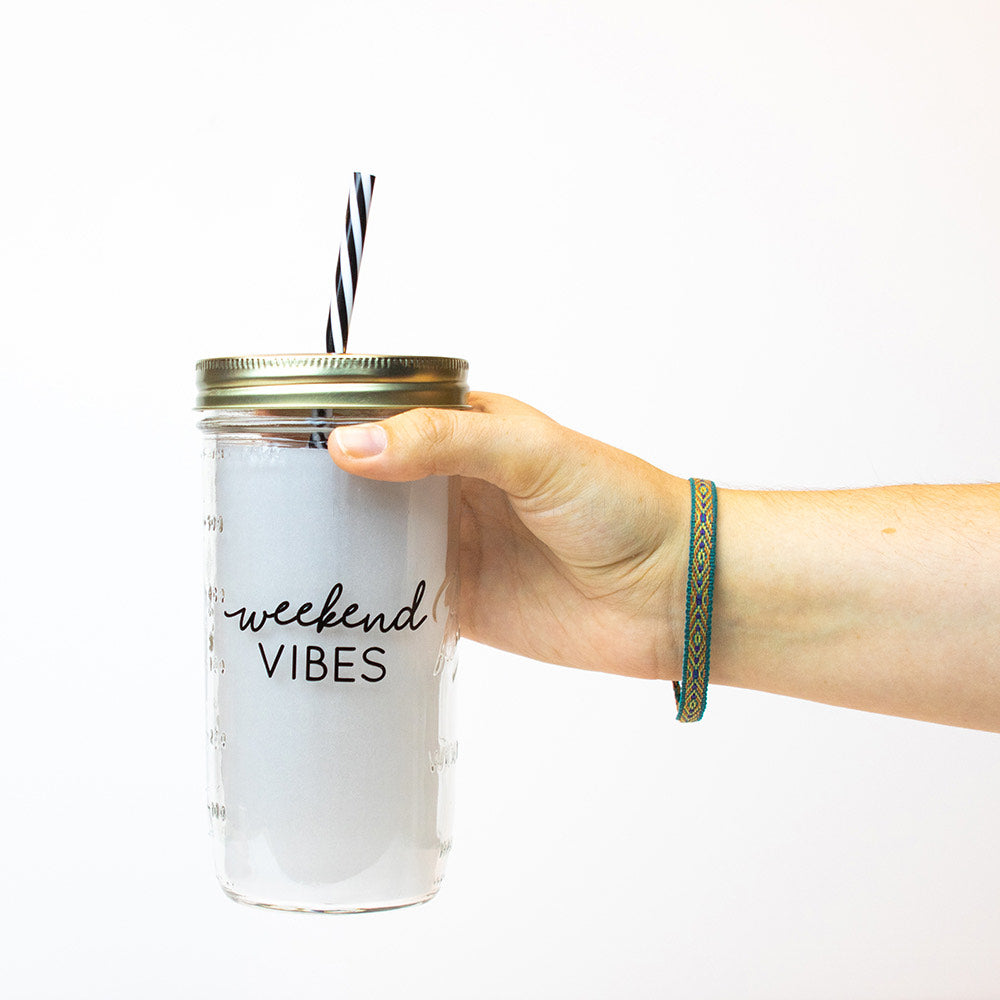 "a hand holds a 24 oz glass reusable mason jar tumbler with a gold straw lid and a black and white stripped reusable straw. on the jar are the words ""Weekend"" in black cursive text, and underneath it ""Vibes"" in black thin block text"