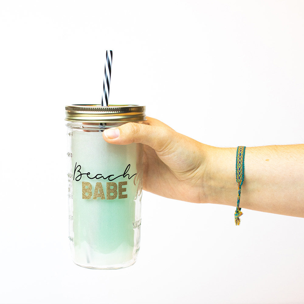 "24 oz reusable glass mason jar tumbler with a gold straw lid and a black & white stripped reusable straw. Text on jar says ""Beach"" in black cursive and ""Babe"" below it in blocked gold sparkle text"
