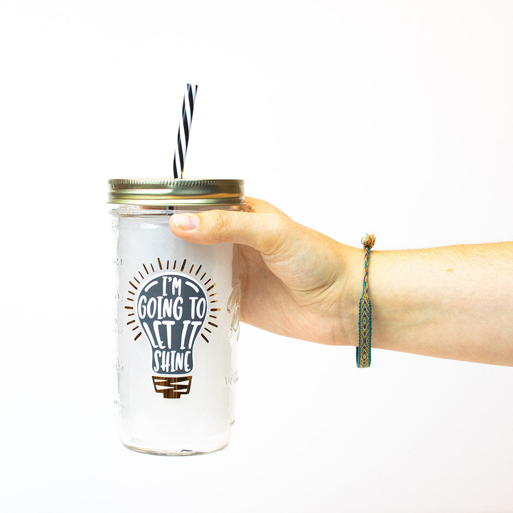 "Hand holding a 24 oz Mason Jar tumbler with gold lid and black and white straw that reads ""I'm going to let it shine"" in black, on a white background"